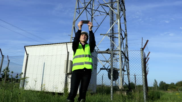 Woman engineer taking pictures of  Wireless communication tower with smartphone .Communication and connection concept - vídeo