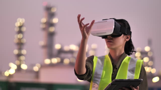 woman engineer wearing virtual reality headset in oil industrial plant at night - rzeczywistość witrualna filmów i materiałów b-roll