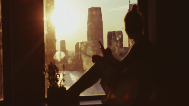vídeos de stock e filmes b-roll de woman enjoy sunset in new york from home - home