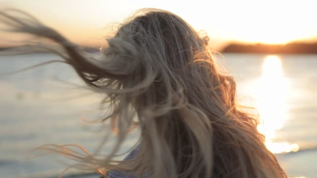 Woman enjoy the nature tossing her hair at sunset video