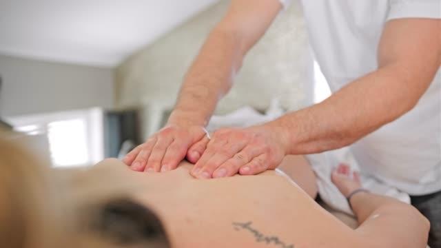 kvinna njuter av en rygg massage - massageterapeut bildbanksvideor och videomaterial från bakom kulisserna