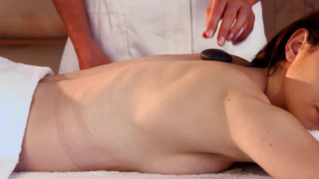 kobieta cieszyć się masaż - terapia lastone filmów i materiałów b-roll