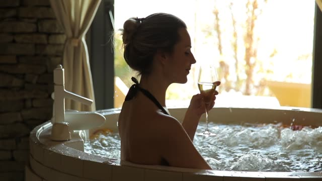 woman enjoying a hot tub while drinking white wine woman enjoying a hot tub while drinking white wine spa treatment stock videos & royalty-free footage