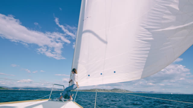 WS Woman enjoying a sailing on a sailboat Wide shot of a woman enjoying a sea breeze on a sailing sailboat. Shoot in 8K resolution. sail stock videos & royalty-free footage