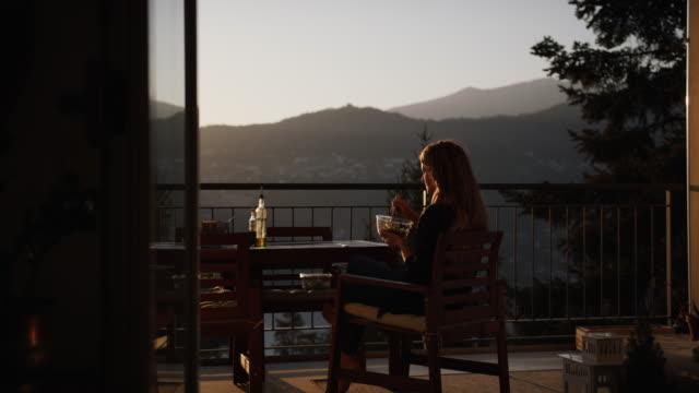 Woman enjoying a salad of microgreens at sunset from behind