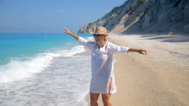 Woman enjoying at the beach Woman enjoying at the Ionian sea beach, unreal blue color of the clear Ionian sea. greek islands stock videos & royalty-free footage