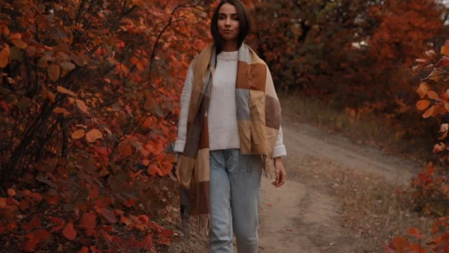 Woman enjoying autumn day, she walking in forest, colorful foliage around, slow motion