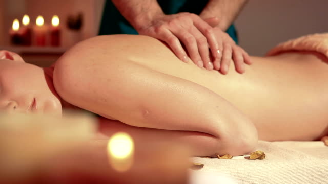 Woman enjoying back massage dolly shot Dynamic video shots of a young woman enjoying spa and massage treatment. Shallow DOF. Technicolor color profile. spa treatment stock videos & royalty-free footage