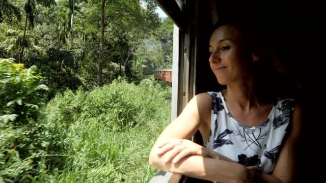 スリランカの電車で美しい風景を楽しむ女性は、茶畑や山を通り抜ける。エラからnエリヤへの有名なルートに乗って電車に座っている女の子 - スローモーション - 乗客点の映像素材/bロール