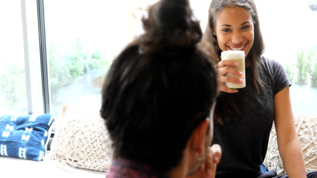 Woman enjoying coffee with friend in cafe video