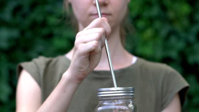donna che si gode il drink dal barattolo di vetro con paglia di metallo, scelta di oggetti riutilizzabili - paglia video stock e b–roll