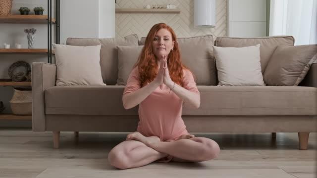 kvinna njuter av fritiden hemma i vardagsrummet. flicka gör yoga på golvet - lotusställning bildbanksvideor och videomaterial från bakom kulisserna