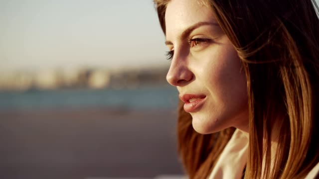 Woman enjoying fresh air by the sea Smiling, young woman is sitting near the sea and enjoying the fresh air. eyes closed videos stock videos & royalty-free footage