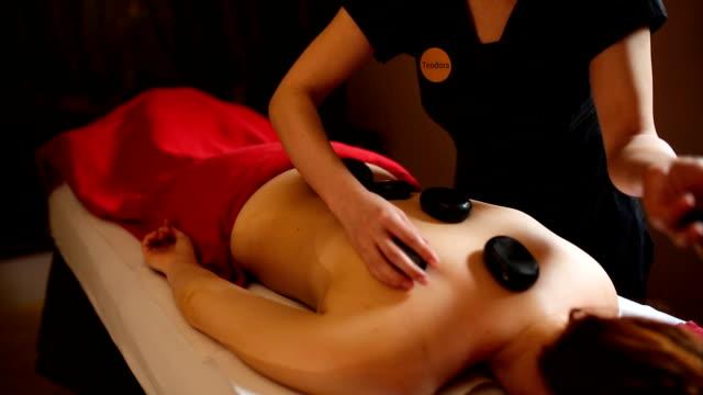 woman enjoying hot stone massage therapy - terapia lastone filmów i materiałów b-roll