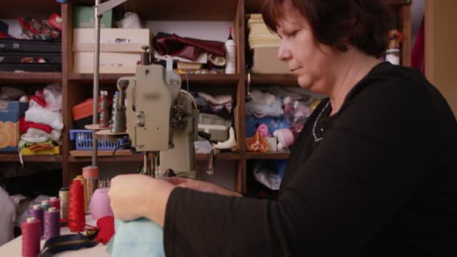 vídeos de stock e filmes b-roll de woman enjoying making and sewing new bag - economia circular
