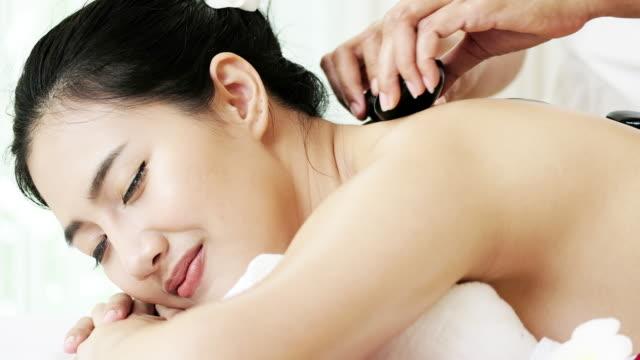 woman enjoying massage for relaxation. - terapia lastone filmów i materiałów b-roll