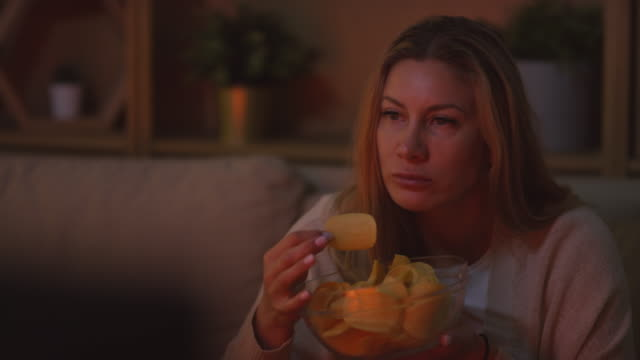 Woman Enjoying Movie in Evening Dolly-in shot of beautiful woman sitting on couch and eating chips while watching interesting movie on TV in evening potato chip stock videos & royalty-free footage