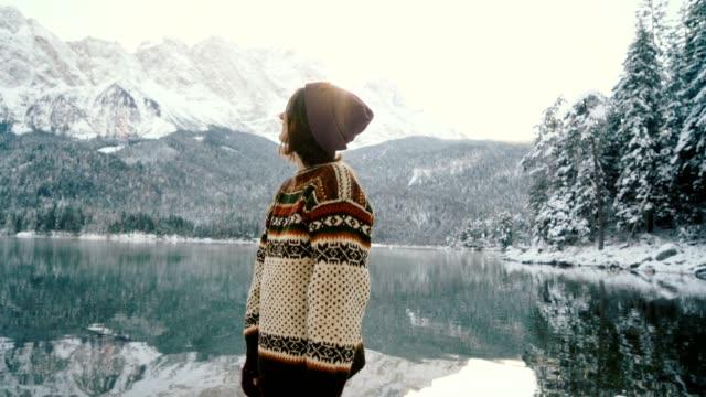 stockvideo's en b-roll-footage met vrouw genieten van schilderachtig uitzicht van eibsee meer in alpen - sneeuwkap