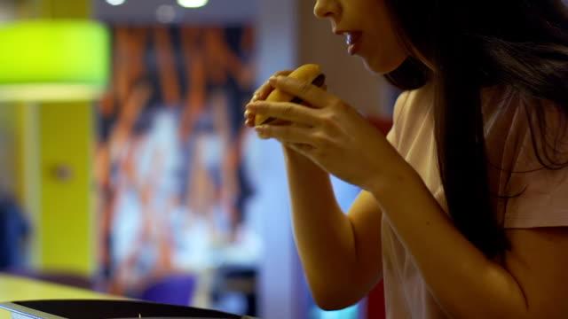 맛과 향의 패스트 푸드 레스토랑에 앉아 햄버거를 즐기는 여자 - burger and chicken 스톡 비디오 및 b-롤 화면