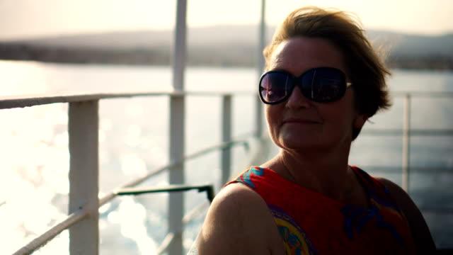 vídeos de stock e filmes b-roll de woman enjoying the sea - 55 59 anos