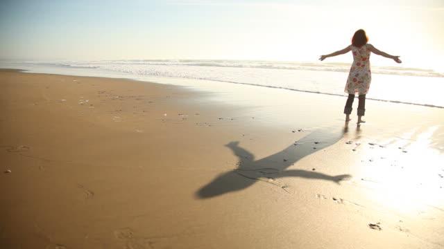 frau genießen sonnenuntergang am strand - einzelne frau über 30 stock-videos und b-roll-filmmaterial