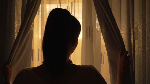 vídeos de stock e filmes b-roll de woman enjoying the sunset by the window. - acordar