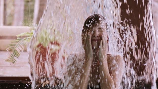 stockvideo's en b-roll-footage met vrouw genieten van waterval massage in de spa van de gezondheid - spa behandeling