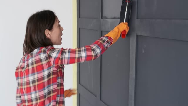 Woman enjoying while painting wooden house wall with a roller