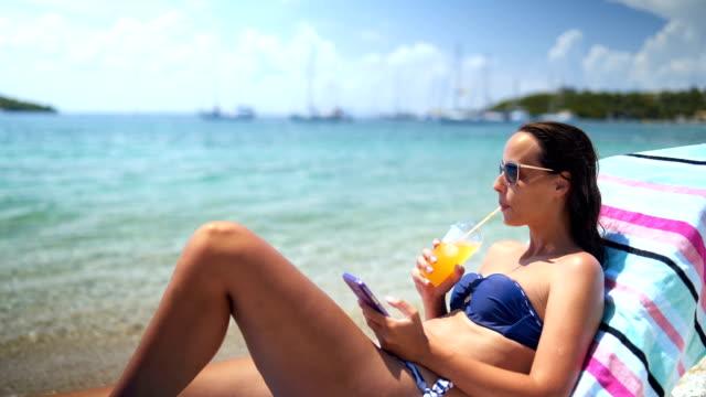 frau genießt einen entspannten sonnentag am meer - sun chair stock-videos und b-roll-filmmaterial