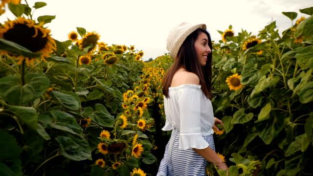 woman enjoys in sunflower field - brązowe włosy filmów i materiałów b-roll