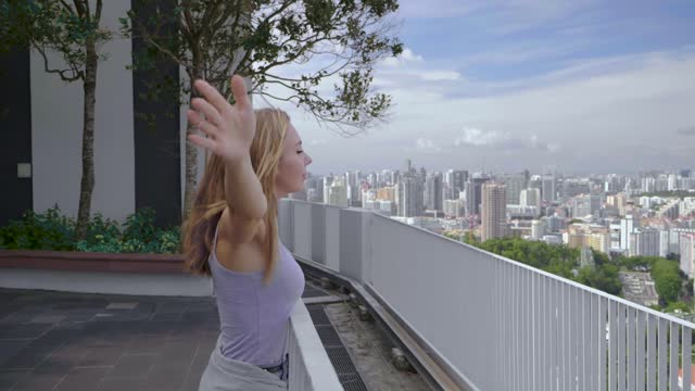 Woman Enjoys Singapore A happy tourist girl holds up her hands and enjoys the stunning view of the skyscrapers in Singapore on a warm summer day. Travel destination, adventure, success and exploration concept. singapore architecture stock videos & royalty-free footage