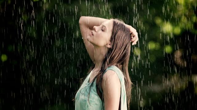 Woman enjoys summer rain on her face video
