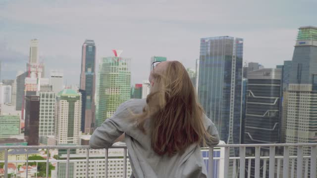 Woman Ennjoying City View Young woman watching the view from skyscraper and cityscape. Urban lifestyle, recreation and leisure concept. Travel destination. singapore architecture stock videos & royalty-free footage
