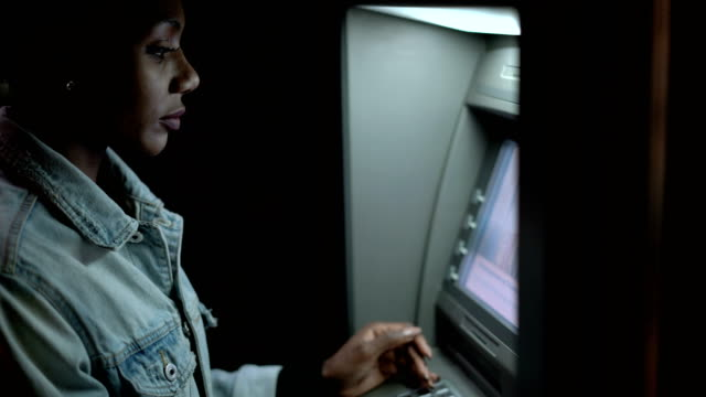 kvinna kommer in på atm-kortkod - spendera pengar bildbanksvideor och videomaterial från bakom kulisserna