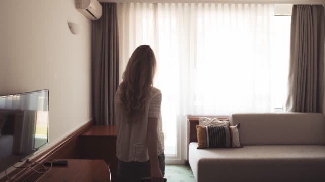 Woman entering hotel room and checking the view Woman entering the hotel room and checking the view hotel stock videos & royalty-free footage