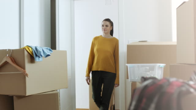 Woman entering in her new apartment full of cardboard boxes video