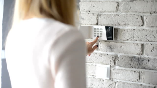 woman entering pin on home security alarm keypad - serratura video stock e b–roll