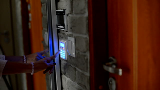 Woman entering pin on home security alarm keypad video