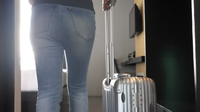 Woman entering to hotel room with her luggage