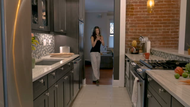 woman enters her galley kitchen dancing with her smart phone - pajamas stock videos & royalty-free footage
