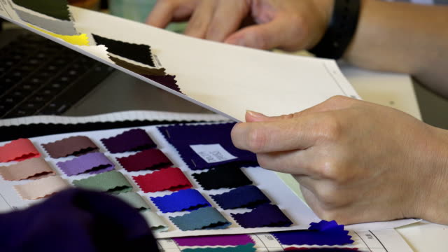 A woman examining fabric swatches