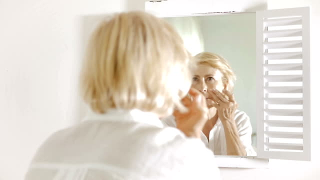 Woman examining her face in the mirror. video