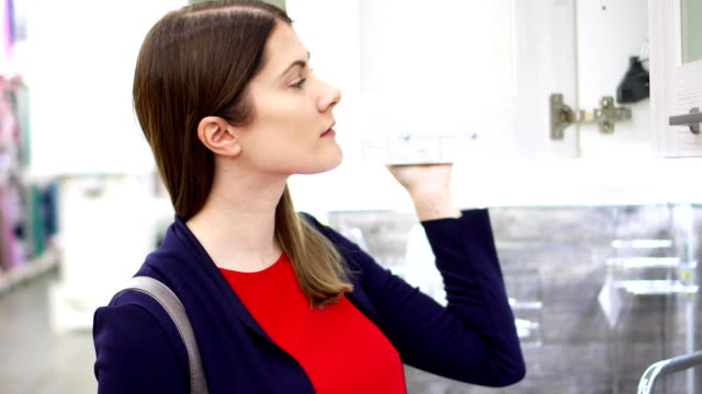 Woman examining kitchen sets in furniture store. Female opening cupboards in modern kitchen showroom video