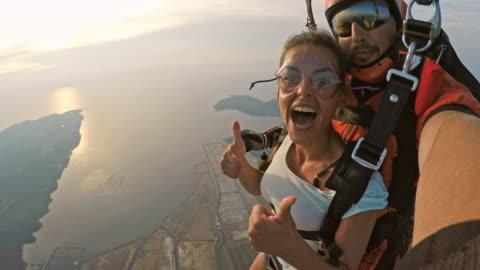 vidéos et rushes de pov femme heureux dans son premier saut en parachute en tandem - courage