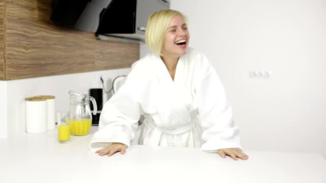vidéos et rushes de femme heureux rire heureux sourire, femme porter un peignoir blanc de cuisine - peignoir