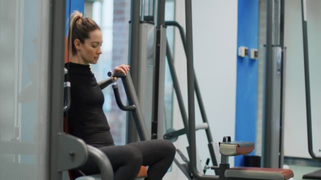 woman exercising at chest press machine.woman training at gym machine.side view, medium shot,slow motion.woman pressing bars doing chest training at fitness club - staw człowieka filmów i materiałów b-roll