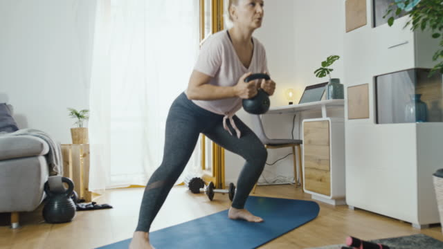 slo mo woman exercising at home - giria filmów i materiałów b-roll