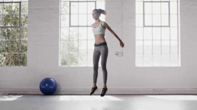 vídeos de stock e filmes b-roll de woman exercising jumping squats in fitness studio - agachar se