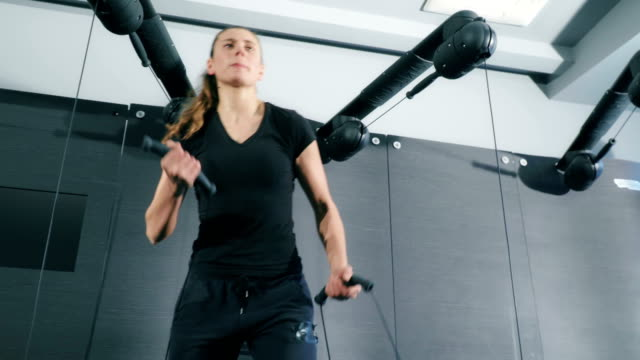 Woman Exercising on Cable Crossover in Gym