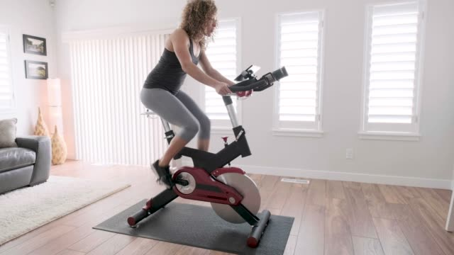 Woman Exercising on Spin Bike in Home A woman exercising on a spin bike using an online instructor inside a home. exercise bike stock videos & royalty-free footage